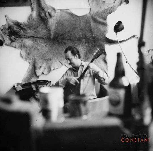 Constant plays guitar in front of lion skin, 1963